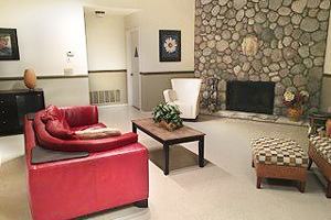 Two comfy chairs & a red couch surround the fireplace area