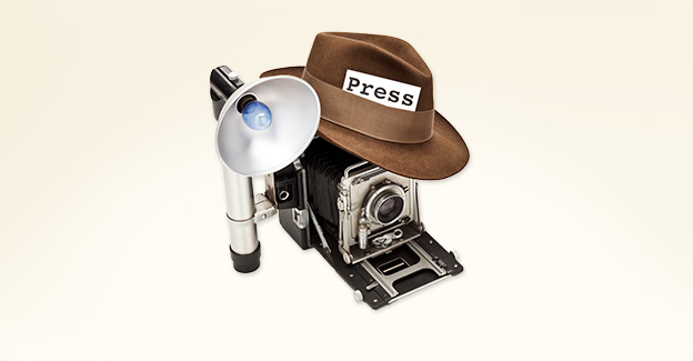 Antique camera and flash with an old hat on top, with a press badge in its band
